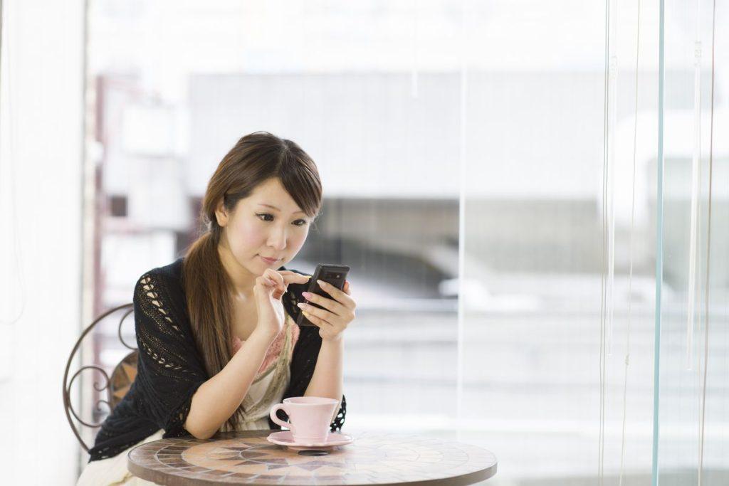 カフェでスマートフォンを使用する女性