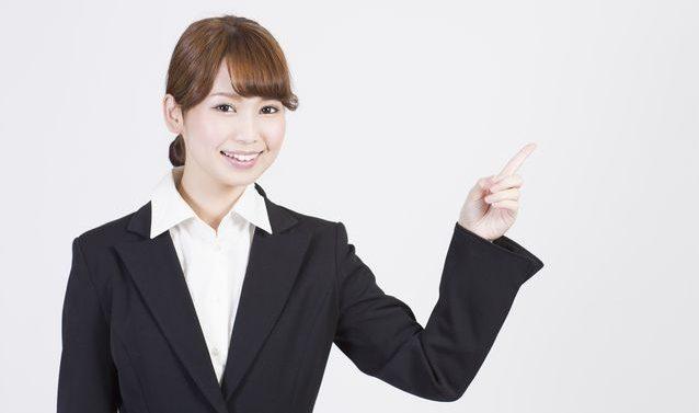 スーツを着た女性が指さしている写真