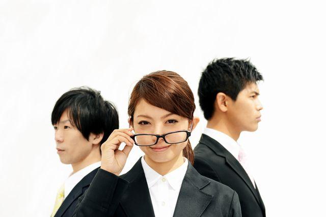 スーツを着た若い女性が眼鏡をかけようとしている写真