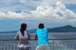 フェリーの甲板で海を眺める若い男女