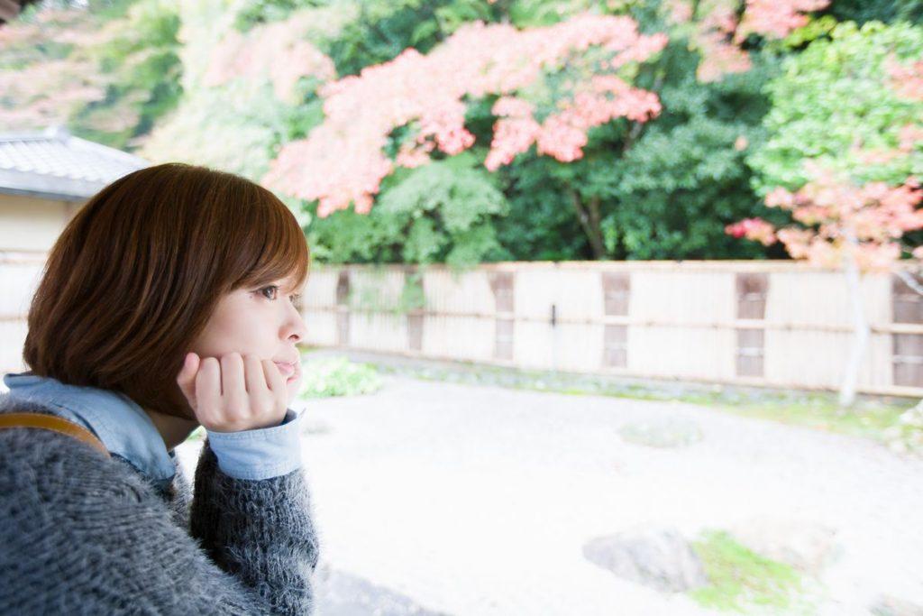 女性が紅葉等の植わっている庭園を見ているところ