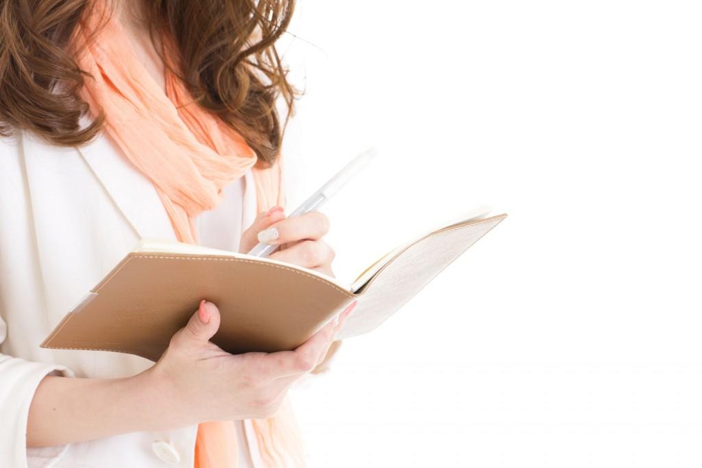 ノートにメモを取る女性