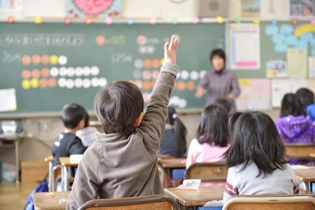 算数の授業で手を挙げる子供の写真